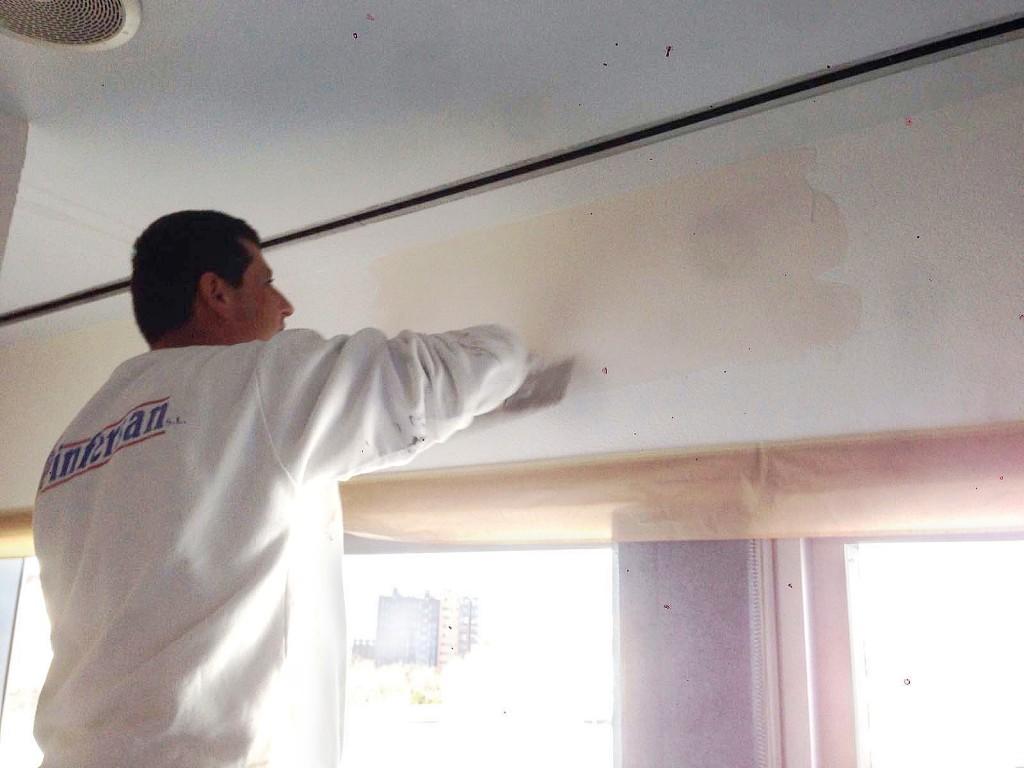 Pintor lijando pared para quitar gotelé.